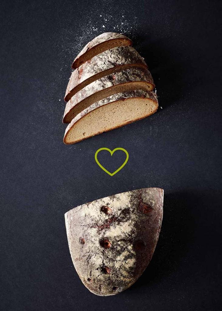 Schräg aufgeschnittenes Brot tabletop auf schwarzem Untergrund - Foodfotografie neon fotografie / huebsch huebsch