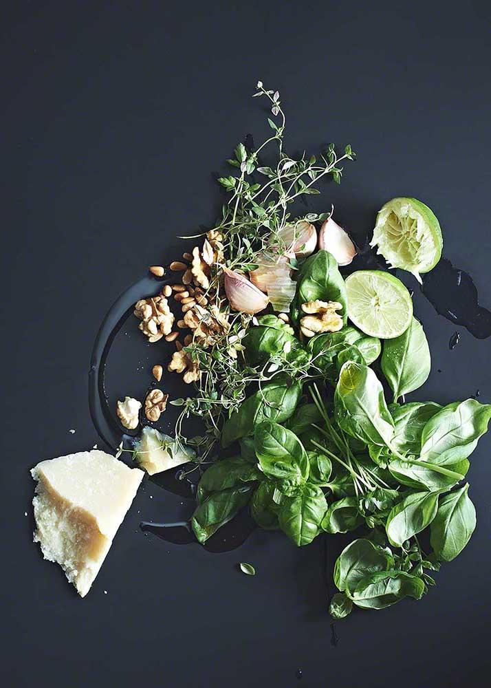 Kräuter, Knoblauch, Parmesan und weitere Zutaten für grünes Pesto auf schwarzem Untergrund - Foodfotografie