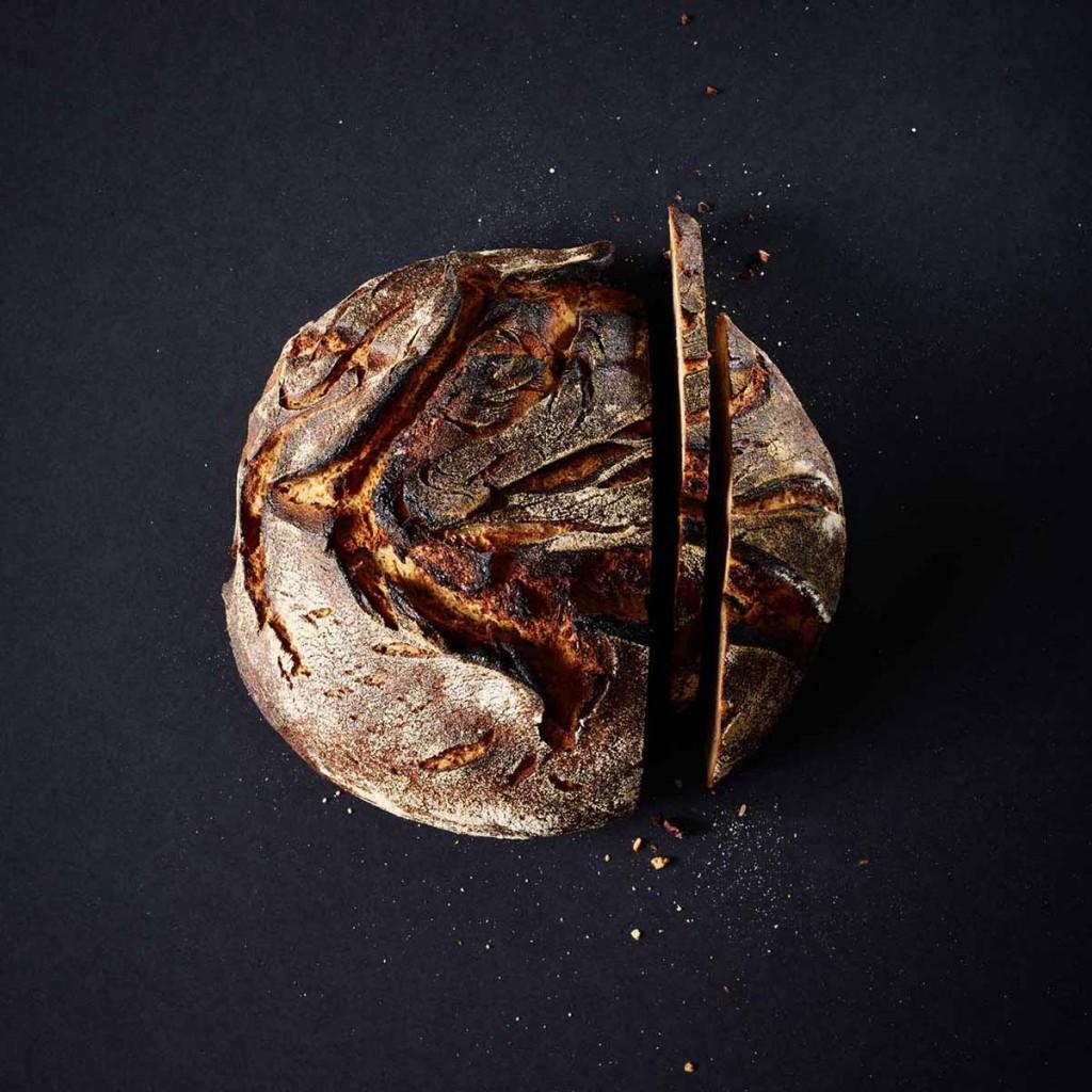 Moderne Foodfotografie von frischem Landbrot auf schwarzem Untergrund - Foodfotografie neon fotografie / huebsch huebsch