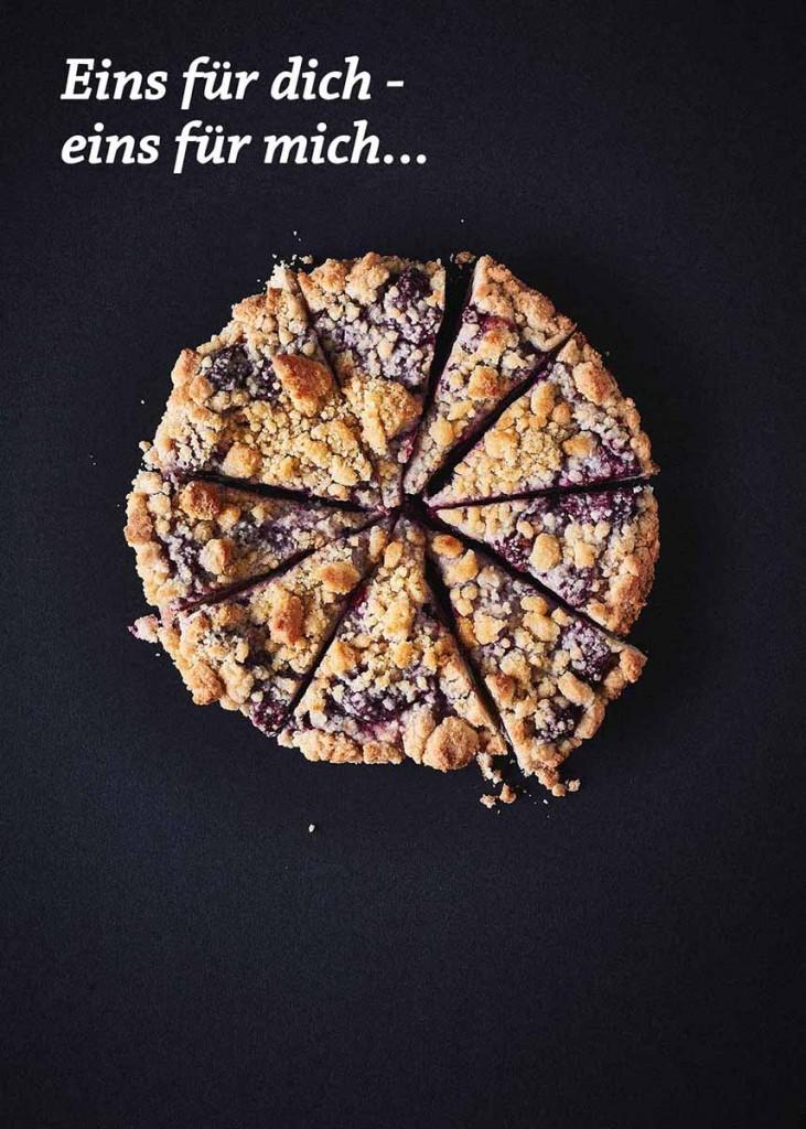 Food-Fotografie eines Kirschstreusel-Kuchen auf schwarzem Untergrund