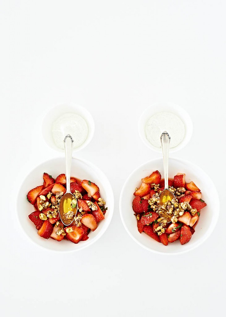 Moderne Food-Fotografie leckeres Dessert mit frischen Erdbeeren, karamellisierten Nüssen und Honig auf weißem Tisch mit viel Freiraum