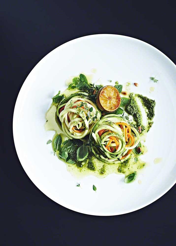 Teller mit gesunder Pasta aus Gemüse auf schwarzem Untergrund
